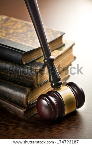 judge gavel with old books on wooden background - stock photo
