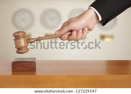 Judge holding gavel against the clock - stock photo