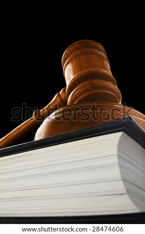 judge's court gavel on a law book, on black - stock photo