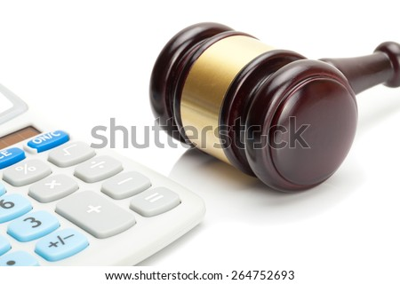 Judge's gavel and calculator right next to it - stock photo