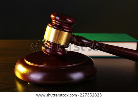 Judge's gavel and green book on dark grey background - stock photo