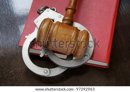 Judge's gavel and handcuffs on red legal book - stock photo