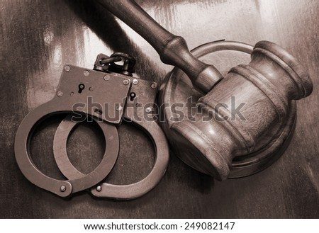 Judge's gavel and handcuffs on table, court concept - stock photo