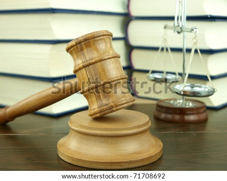 Judge's Gavel and scale of justice with a stack of legal books background - stock photo