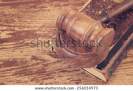 Judge's gavel and very old legal book on wooden background - stock photo