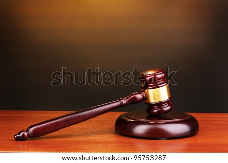Judge's gavel on wooden table on brown background - stock photo
