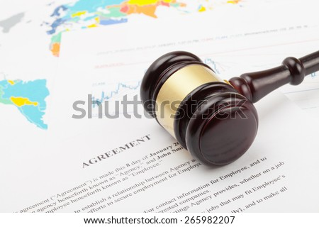 Judge's gavel over agreement documents and world map - stock photo