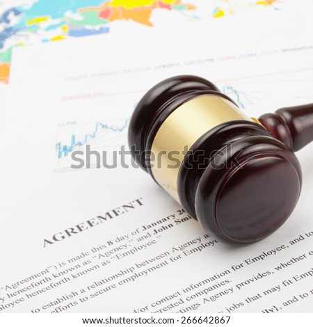 Judge's gavel over agreement documents and world map - close up shot - stock photo