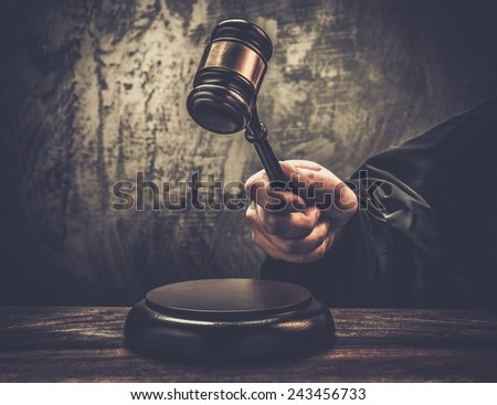 Judge's hand holding wooden hammer  - stock photo
