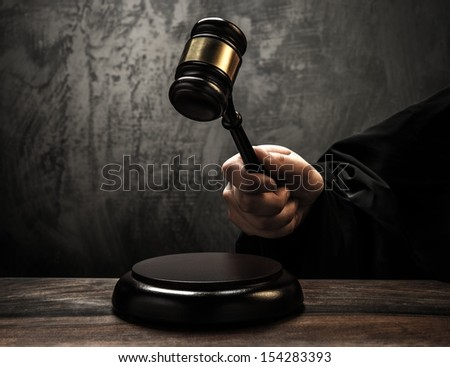 Judge's holding wooden hammer  - stock photo