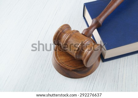 Judge's wooden gavel and blue legal book on white table - stock photo