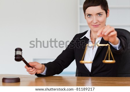 Judge with a gavel and the justice scale in her office - stock photo