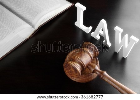 Judges Gavel, Red Open Legal Book And White Sign LAW From Wood Latter On The Black Table In The Back Light. Overhead View. - stock photo