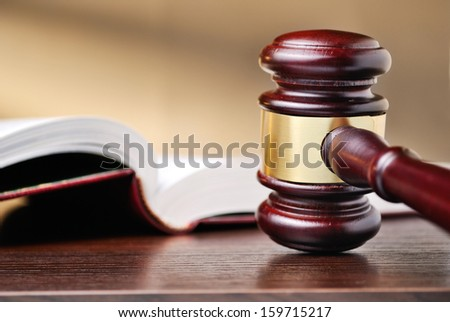 Judges wooden gavel with a brass band around the mallet standing upright on a wooden counter top alongside a law book conceptual of judgements and law enforcement - stock photo
