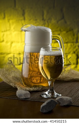 Jug and glass with beer in an interior - stock photo