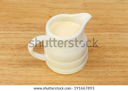 Jug of cream on a wooden board - stock photo