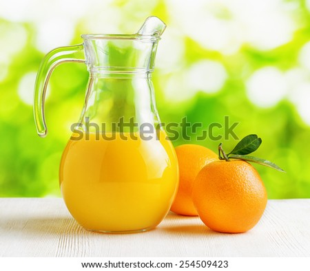 Jug of orange juice and oranges on nature background. Eco food rich in minerals and vitamins. Product of organic farming. - stock photo