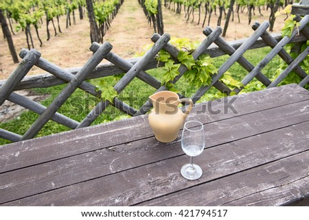 jug of wine and a glass on a background of vineyard - stock photo