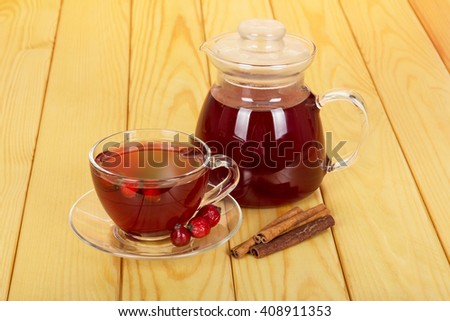 Jug with a drink and a cup of tea rosehip berries on a background of light wood. - stock photo