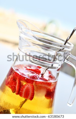 Jug with Champagne Sangria on the cafe table - stock photo
