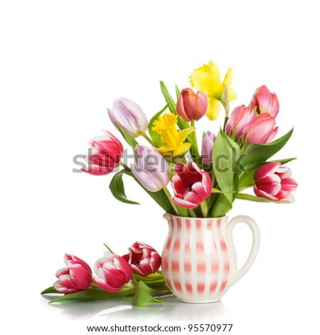 Jug with spring flowers on white background - stock photo