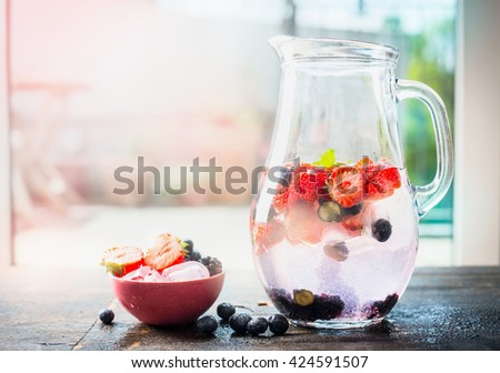 Jug with summer drink with water and berries. Berries lemonade on terrace table over nature background.  Detox drink, diet and health food concept - stock photo