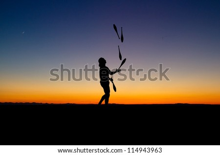 juggler in sunset with five juggling clubs - stock photo