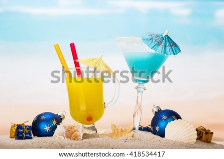 Juice cocktail starfish, seashells, christmas balls and gifts in the sand against the sea. - stock photo