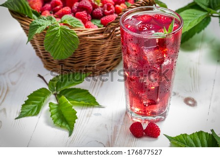 Juice from freshly harvested raspberries served with ice - stock photo