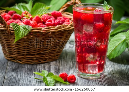 Juice of fresh raspberries served with ice in a glass - stock photo