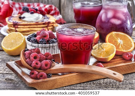 juice of raspberries and blackberries with citrus and pancakes on the table - stock photo