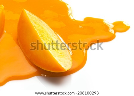 Juice splat and slice of Alphonso Mango - stock photo