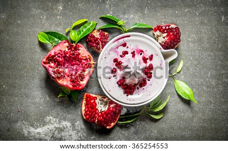 Juicer with bits of pomegranates and leaves. On the stone table. Top view - stock photo