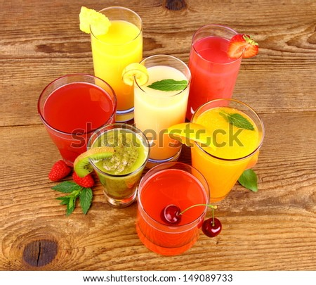 Juices from kiwi, raspberries, cherry, orange, strawberry and pineapple, top view - stock photo