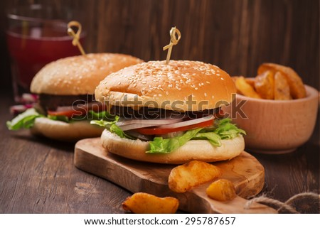 Juicy and fragrant hamburgers with fries on wooden rustic table. Selective focus - stock photo