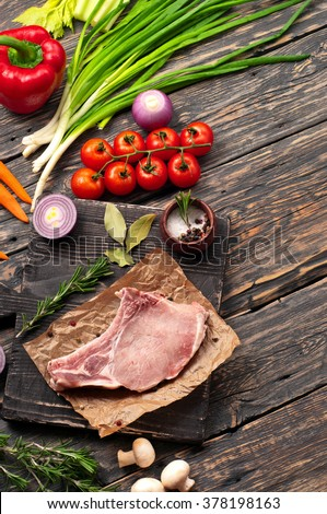 Juicy and fresh piece of pork steak on the bone with vegetables on a cutting board on a dark rustic table, top view with copy space. Raw ingredients for the preparation of tasty and healthy food - stock photo