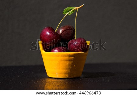 Juicy and ripe cherry in ceramic basket with water drops on a black background - stock photo