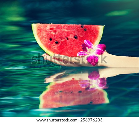 Juicy and ripe slice of watermelon in  hand above the water - stock photo