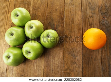 Juicy apples and orange on wooden table - stock photo