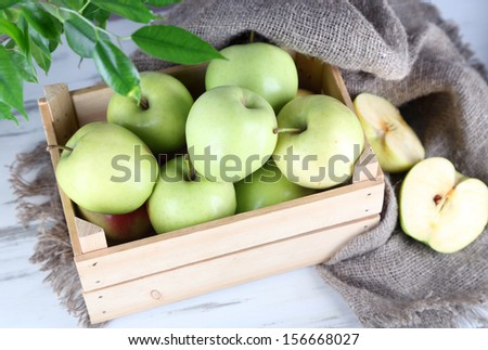 Juicy apples in box on wooden table - stock photo