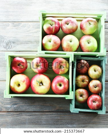 Juicy apples in boxes on wooden background - stock photo