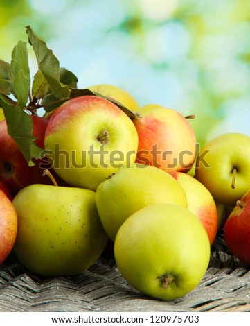 juicy apples with leaves, on green background - stock photo