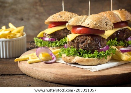 Juicy beef burgers with melted cheese.Selective focus on the front burger - stock photo