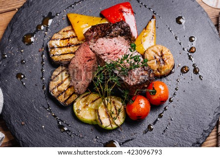 Juicy Beef rump steak from marble beef medium rare with spices and grilled vegetables on black stone plate, close-up. Selective focus. - stock photo