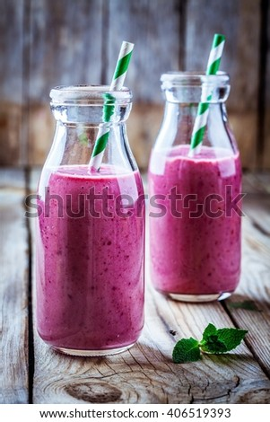 juicy blackberry smoothies in glass bottles on wooden table - stock photo