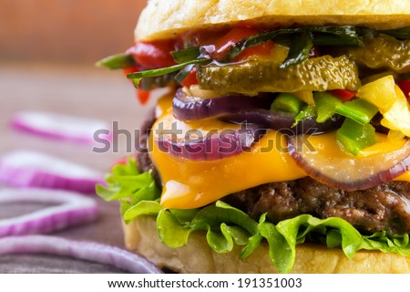 Juicy burger closeup with roasted vegetables and grilled beef putty  - stock photo