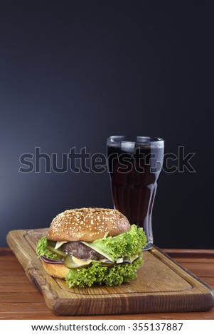 juicy burger on a table with a cold drink - stock photo