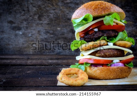 Juicy cheeseburger on the wooden background - stock photo