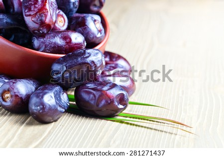 juicy dates in a brown dish on wooden table - stock photo