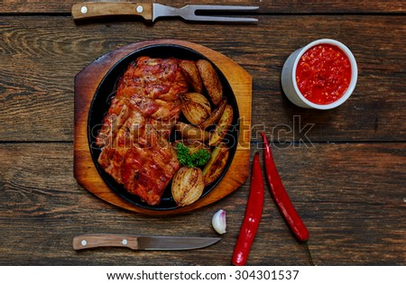 Juicy delicious meat cooked on the grill with vegetables decorated with greenery, a perfect dish meksikansiky hot sauce - stock photo
